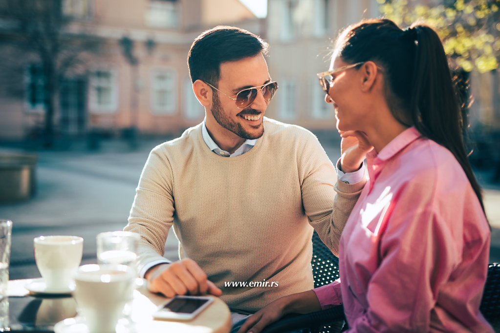 Affectionate smiling couple embracing while sitting in cafe.