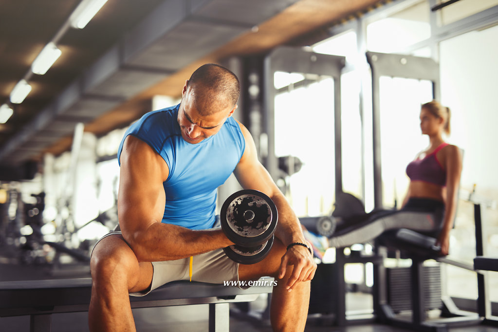Young muscular man lifting up dumbbells at the gym.
