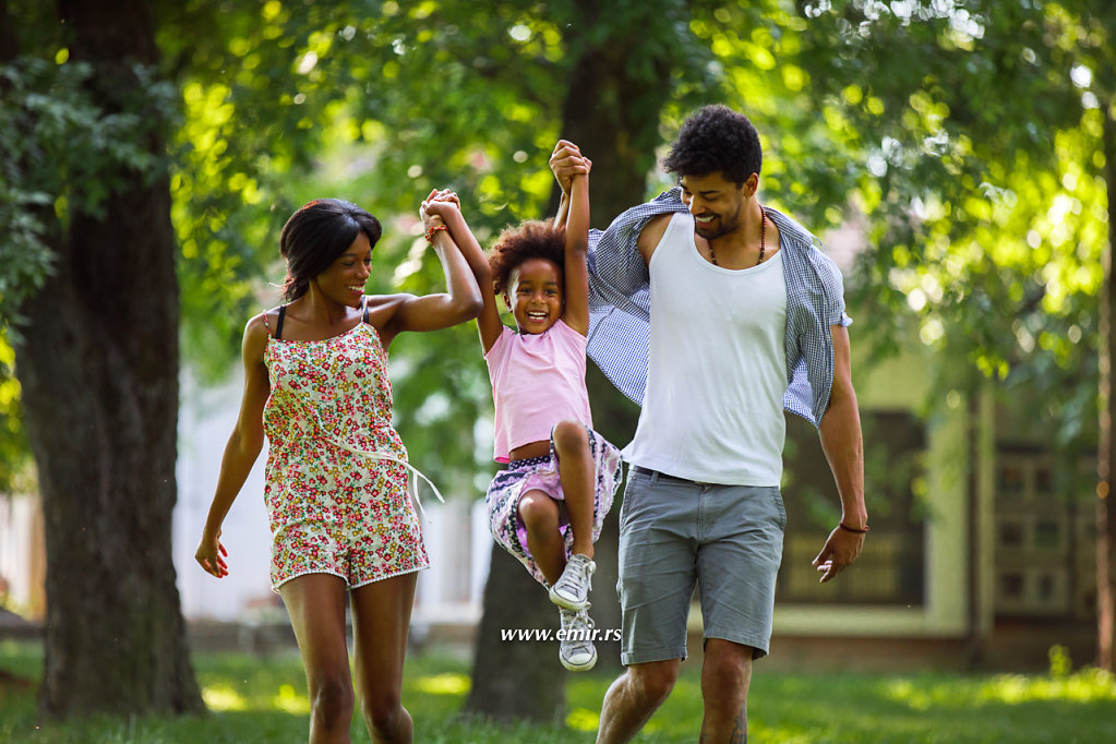 Happy African-American family running and swinging their daughter