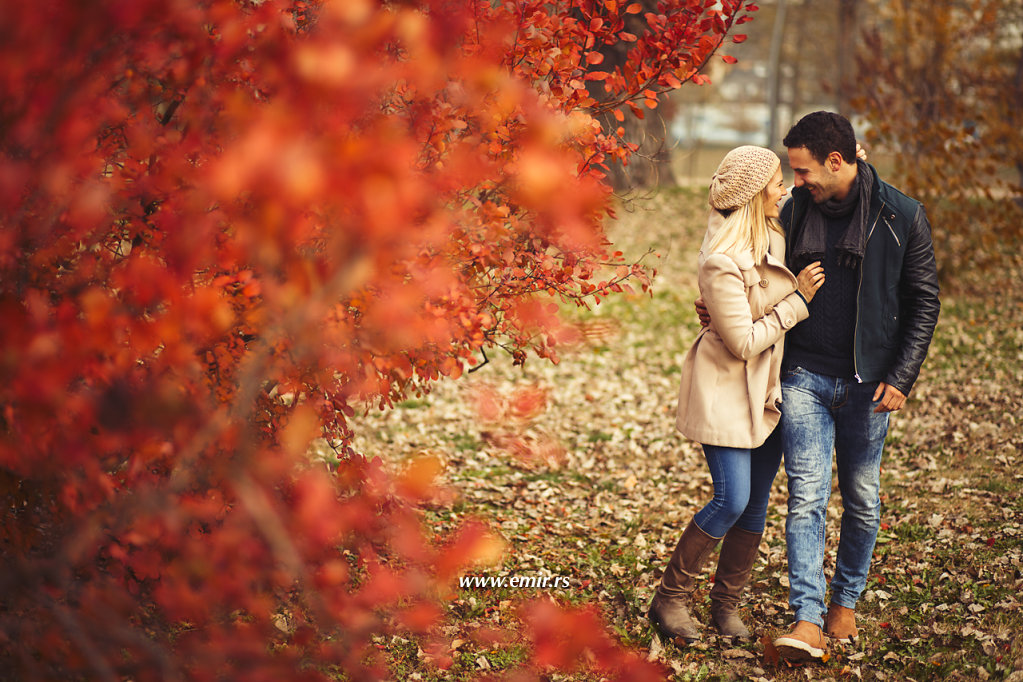 Young embraced couple taking a walk in autumn park.